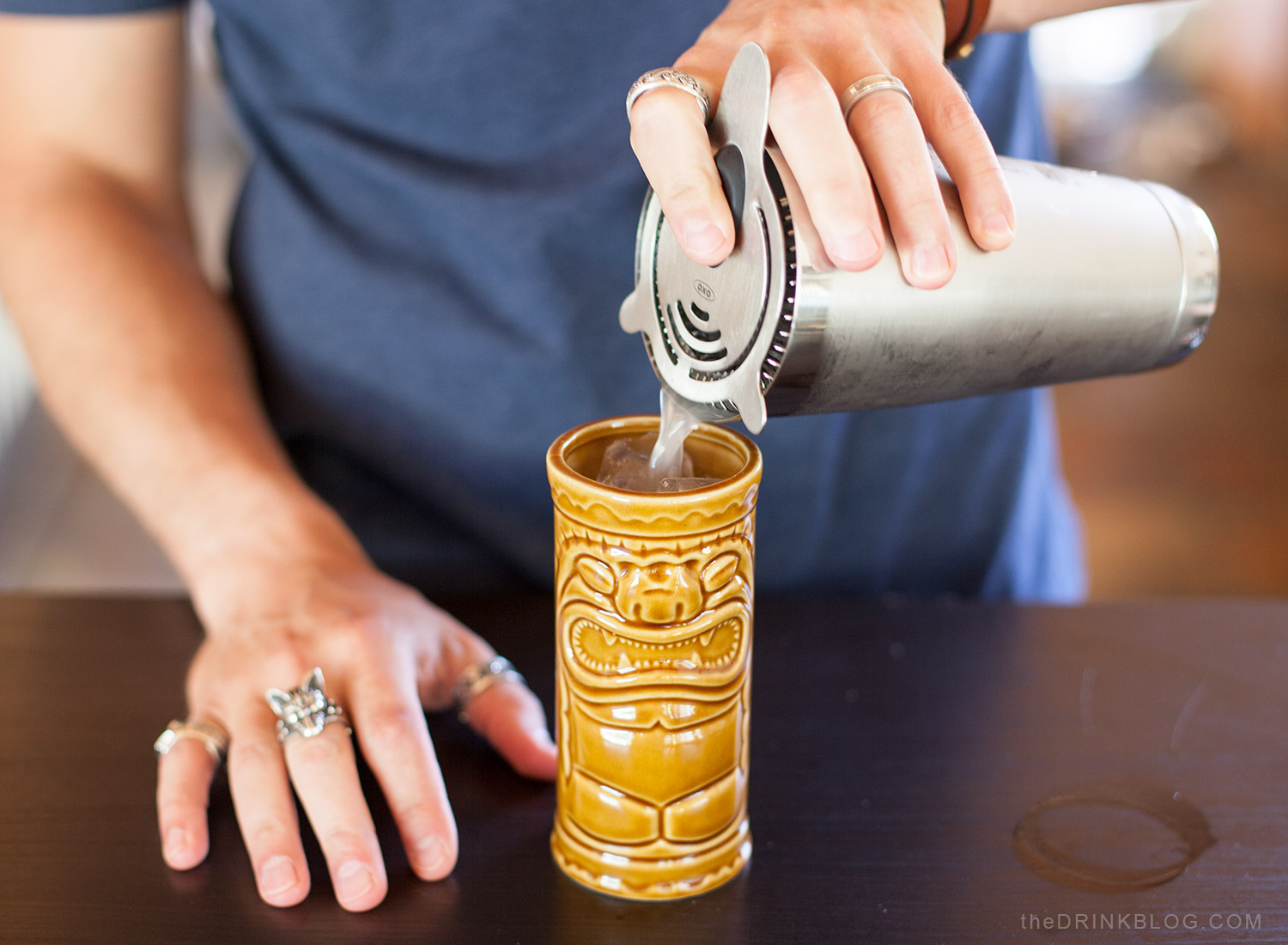 pour cocktail into tiki mug